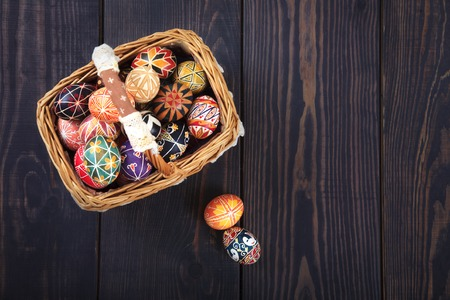 Easter decorated eggs in the basket, on a wooden background. Copy space, easter background. Stock Photo