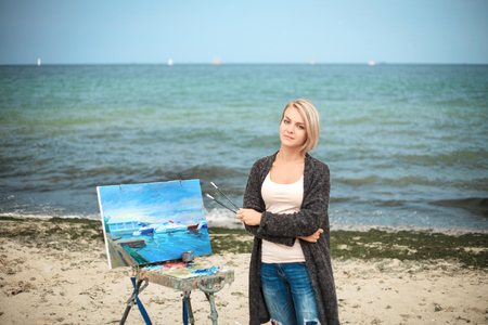 Beautiful young woman painting on the background of the sea and sky. Beautiful portrait of the painter on outdoor. Stock Photo