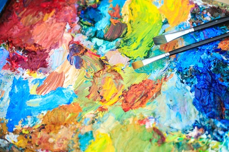 Color background of the artists palette with brushes. Multi-colored oil paints on the palette. Stock Photo