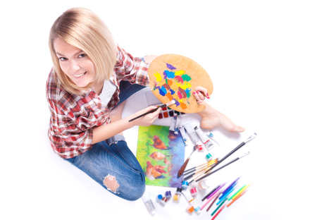 Top view of woman holds in her hands a palette around paint and materials for creativity.