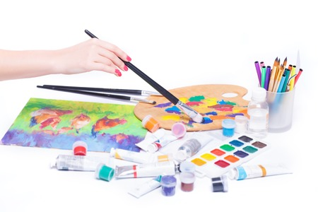 Drawing a picture, female hand close-up, stationery, paint brushes, on a white background in the studio. Stock Photo