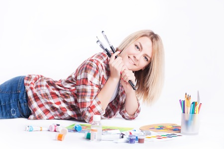 Portrait of a young woman with brushes in her hands in the studio on a white background. Stock Photo