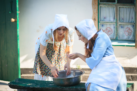 Two beautiful young women washing their hands in the countryside with water from a bowl. Rertro rural style. Stock Photo