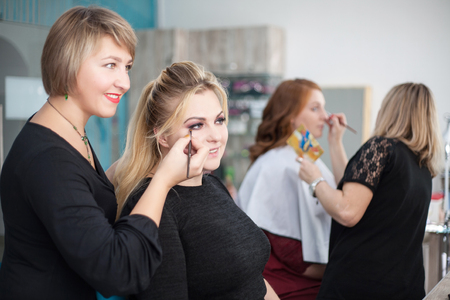 Professional makeup artist working on young girl makes makeup in a beauty salon Stock Photo