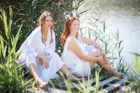 Two young women in long white dresses near the river. Sunny summer day. Stock Photo