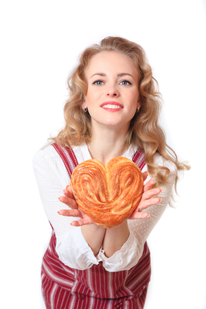 Portrait of cute smiling woman with pastries in her hands in the studio on white background