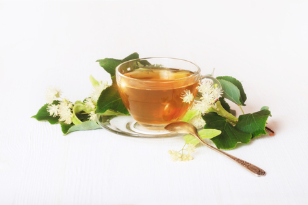 Linden tea on a white table in a glass cup. Flower tea, herbal medicine.