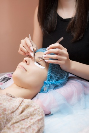 Procedure of eyelashes extension in salon close up