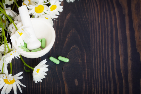 Chamomile flowers and green phytotherapeutic capsules on a wooden table. Herbal medicine and health