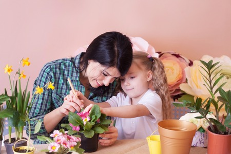 Cute child girl helps her mother to care for plants. Happy family on a studio.