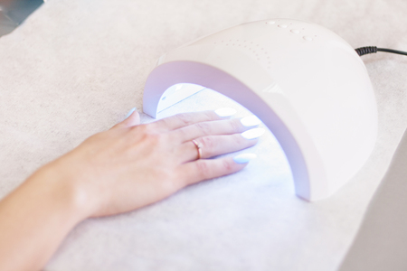 Woman using UV light dryer. Manicure, spa salon concept. Beauty and fashion. Close up. Stock Photo