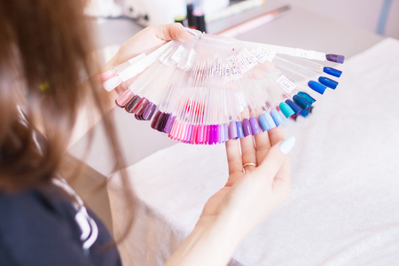 Young woman hands choosing nail color. Female manicured hands and nail color samples, beauty salon.