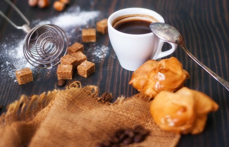 Cup of hot black coffee with home made profiteroles on a rustic wooden table