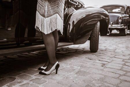 Beine der Frau nahe altem Auto Junge Frau in Schuhen mit hohen Absätzen, Retro-Stil. Standard-Bild