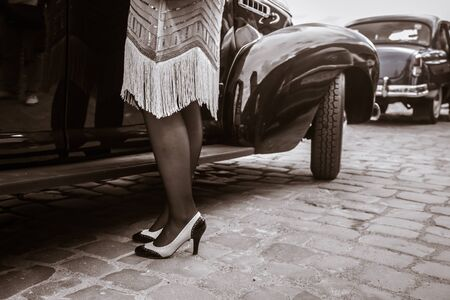 Legs of woman near old auto. Young woman in high heels shoes, retro style.