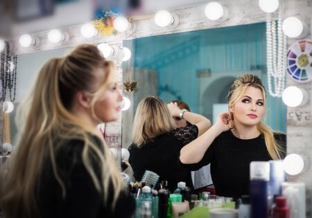 Woman in a beauty salon looks at her reflection in the mirror on her makeup and hairstyle. Real people. Stock Photo