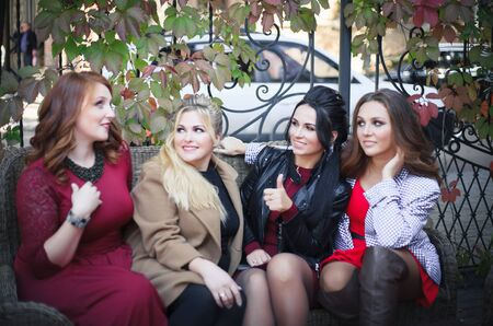 Four women have fun talking when they meet in the fall in an outdoors cafe.