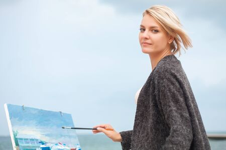 Beautiful young woman painting on the background of the sea. Beautiful portrait of the painter on outdoor.