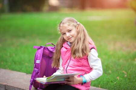 Little school girl with a backpack and book walking outdoors after lessons, read book or study, education and learning concept.