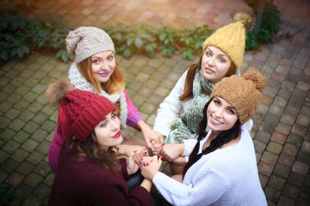Girls in warm knitted clothes and hats hug, top view. Autumn day, a group of friends. Positive emotions. Banco de Imagens