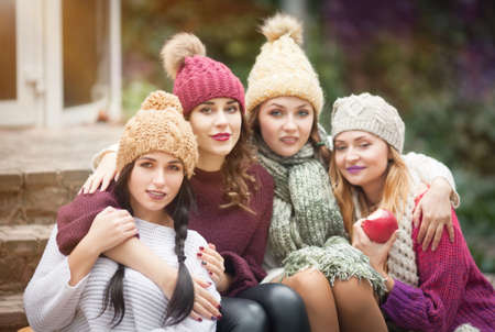Women are best friends with fruit on a picnic in the countryside. Outdoors lifestyle fashion portrait. Positive emotions.