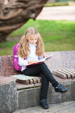 Little school girl with a backpack and book walking outdoors after lessons, read book or study, education and learning concept. Banco de Imagens - 152407040