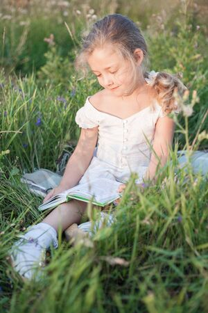 Little girl with a book in her hands on a meadow in a summer day.