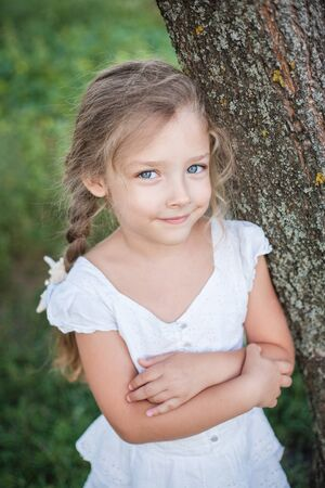 Closeup portrait of a beautiful little girl outdoors in summer.
