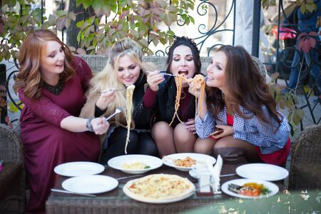 Four young women having lunch in a cafe. Pasta in a summer cafe.