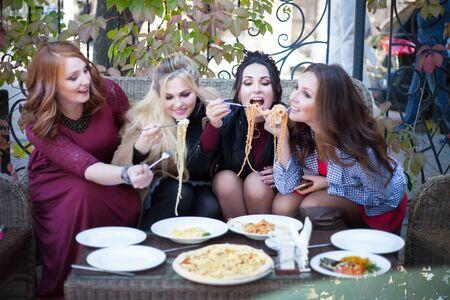 Vier junge Frauen essen in einem Café zu Mittag. Pasta in einem Sommercafé.