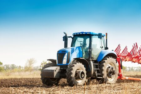 The tractor plows the field, cultivates the soil for sowing grain. The concept of agriculture. Stok Fotoğraf