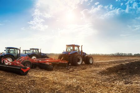 Several tractors plows the field, cultivates the soil for sowing grain. The concept of agriculture. Stok Fotoğraf - 133811037