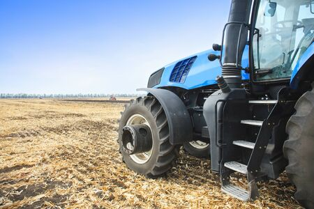 Modern tractor in the field during planting. The concept of agricultural industry. Stock Photo