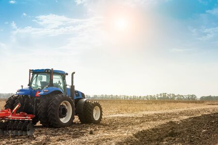 The tractor plows the field, cultivates the soil for sowing grain. The concept of agriculture. Stok Fotoğraf - 133811160