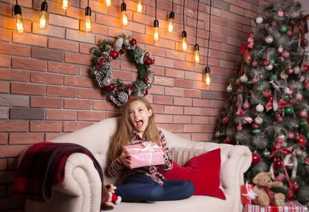 Little school age girl with a Christmas gift in her hands. Stock Photo