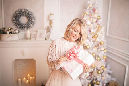 Young beautiful blonde woman holding a gift box. Christmas and new year concept.