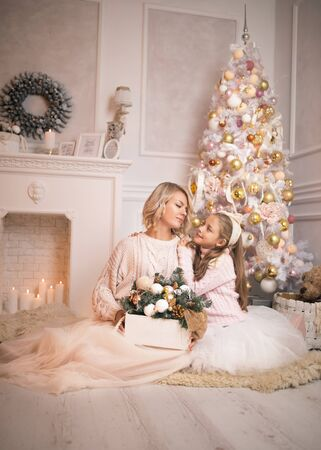 Portrait of a joyful mom and daughter against the background of the Christmas interior. Stok Fotoğraf