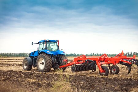 Modern tractor in the field during planting. The concept of agricultural industry. Copy space.