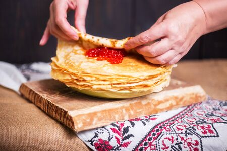 Woman wraps red caviar in a hot pancake in the kitchen, hands closeup. Rustic style, crepes close-up. Stok Fotoğraf