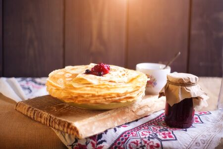 Homemade hot pancakes with jam. Rustic style, crepes close-up.