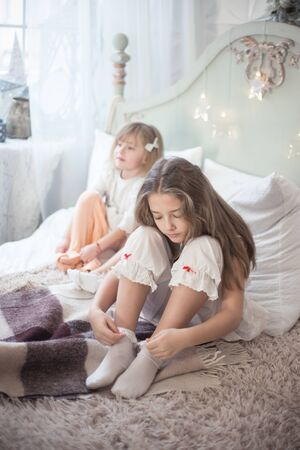 Two sisters in the bedroom dress in the morning. Girls in pajamas on the bed.