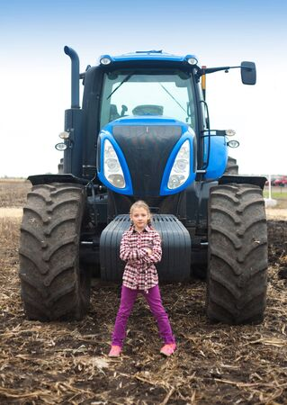 Cute girl near the modern tractor in the field. The concept of field work, agricultural machinery. Imagens - 143138248