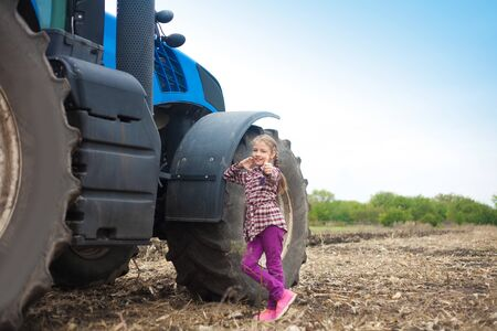 Cute girl near the modern tractor in the field. The concept of field work, agricultural machinery. Imagens