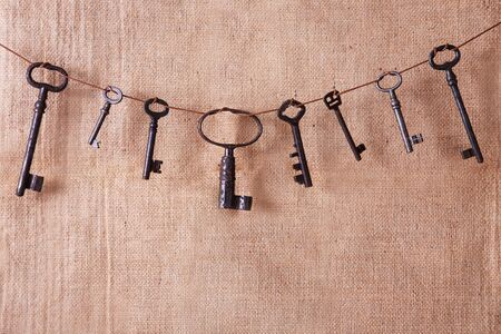 Several old rusty keys on a burlap background. Retro and vintage, steampunk. Copy space.