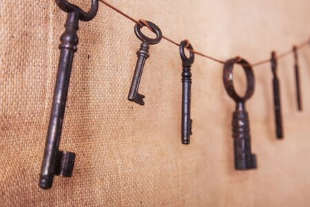 Several old rusty keys on a burlap background. Retro and vintage, steampunk. Banco de Imagens