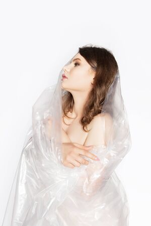 Young beautiful woman in plastic in the studio. Ecology and plastic trash concept.