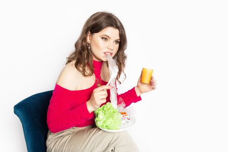 Young beautiful woman eating a plastic bag as a concept of plastic contaminated food. Ecology and healthy eating concept. Studio shot.. Hight quality photo