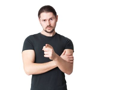 Young serious man points a finger in front of himself. Isolated on a white background. Banco de Imagens