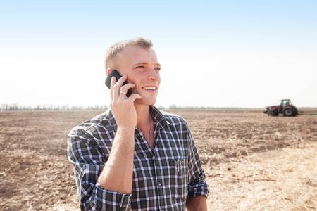 Young attractive man with telephone near a tractor. Concept of agriculture and field works. Banco de Imagens