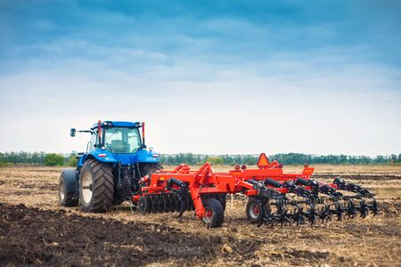 Modern tractor working in a field on a bright sunny day. The concept of work in a fields and agriculture industry.